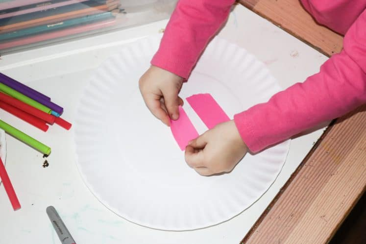 preschooler adding colorful tape to paper plate
