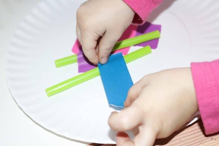 preschooler attaching straw to paper plate using colorful tape