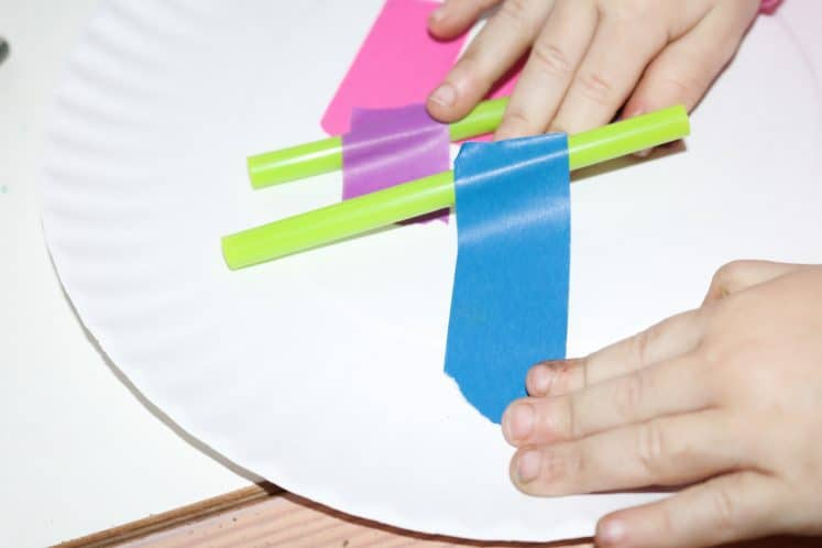 preschooler making a wheel with paper plate, straws, and colorful tape