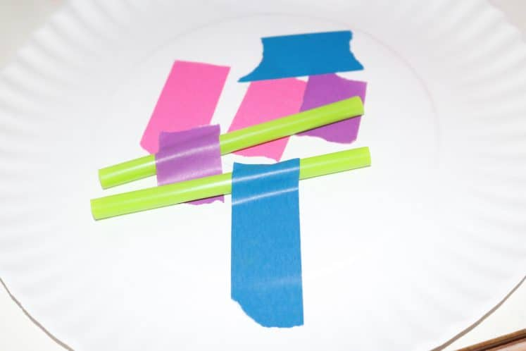 straws attached to paper plate with colorful tape