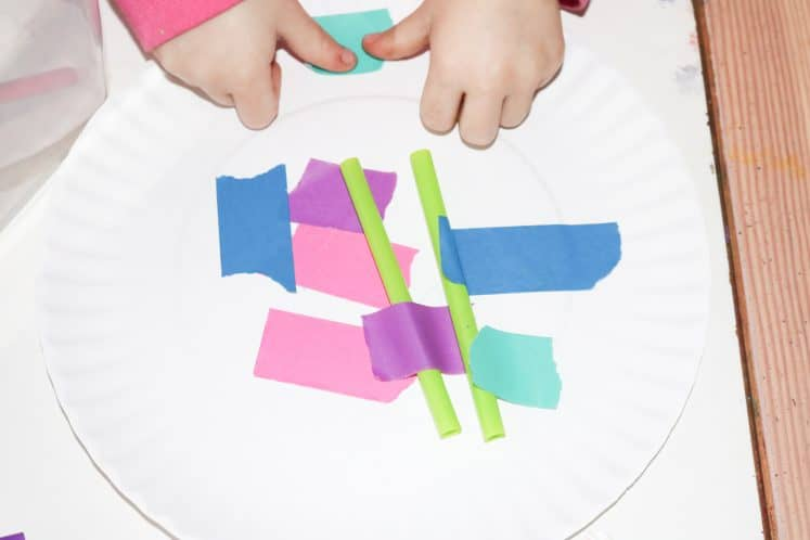 preschooler making wheel using paper plate, straws, and colorful tape