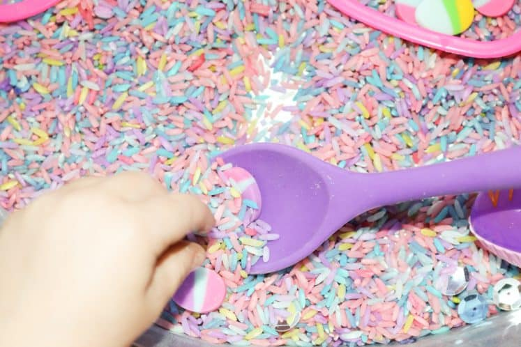 child using spoon to scoop colored rice