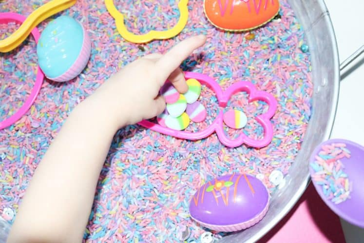 child placing Easter mini erasers in the center of carrot cookie cutter