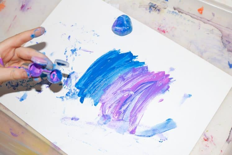 child making galaxy art with pink and blue paint