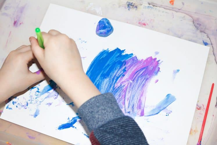 child making galaxy process art using paint on white cardstock