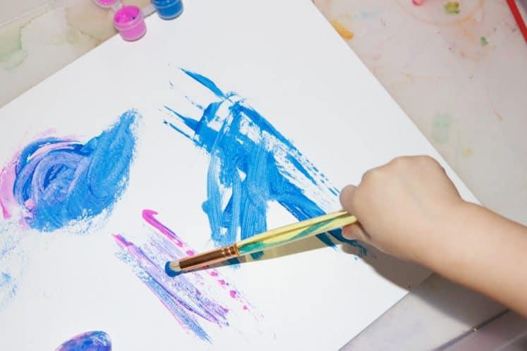 preschooler making galaxy art using paintbrush