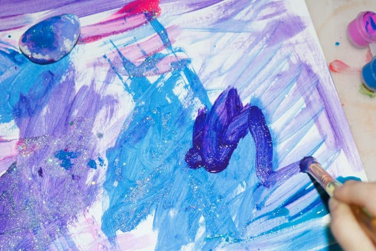 child's galaxy process art using pink, blue, and purple paint colors