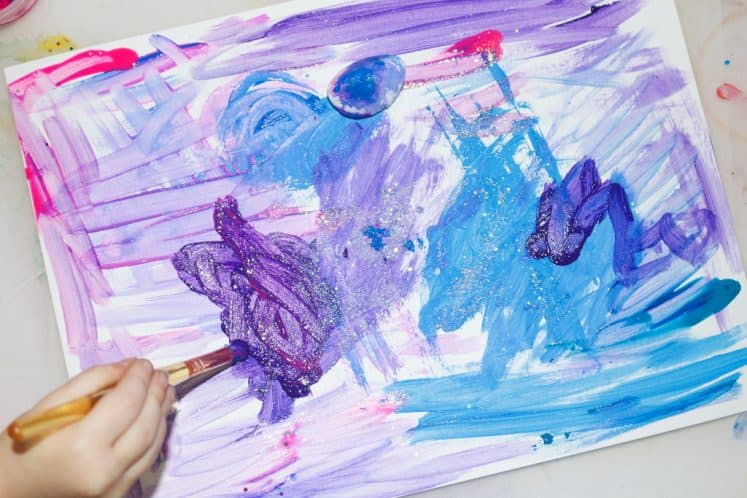 preschooler painting galaxy art using paintbrush