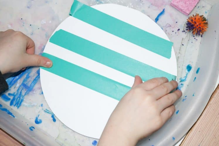 child making stripes with tape on cardstock circle