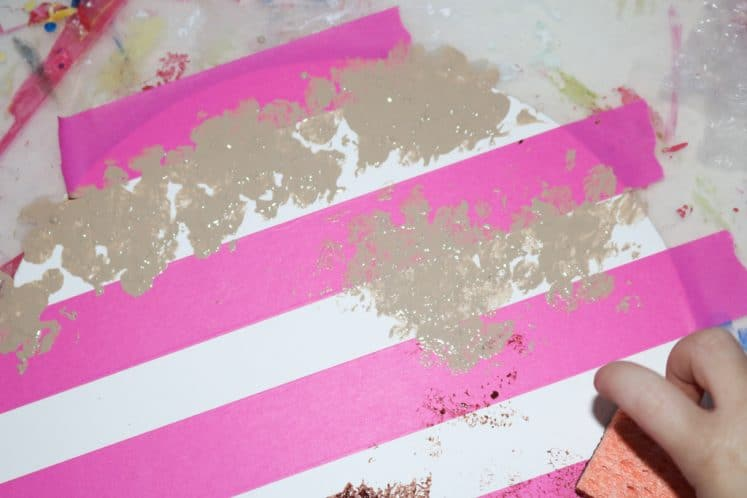 child making stripes with sponge and paint
