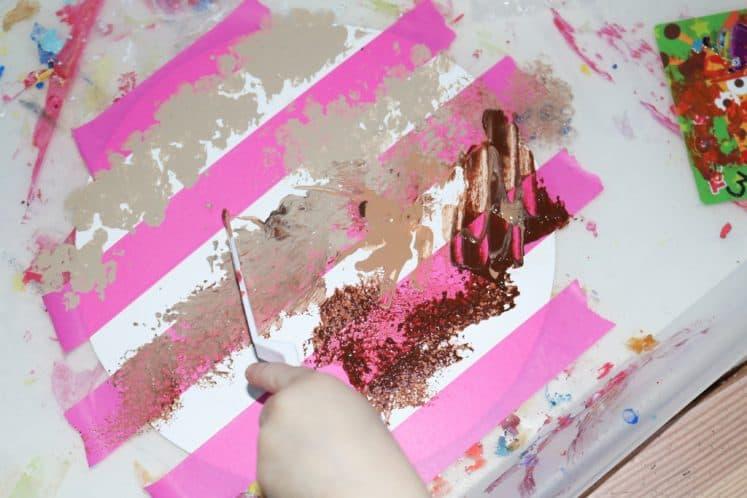 child using spatula to spread paint on Jupiter process art