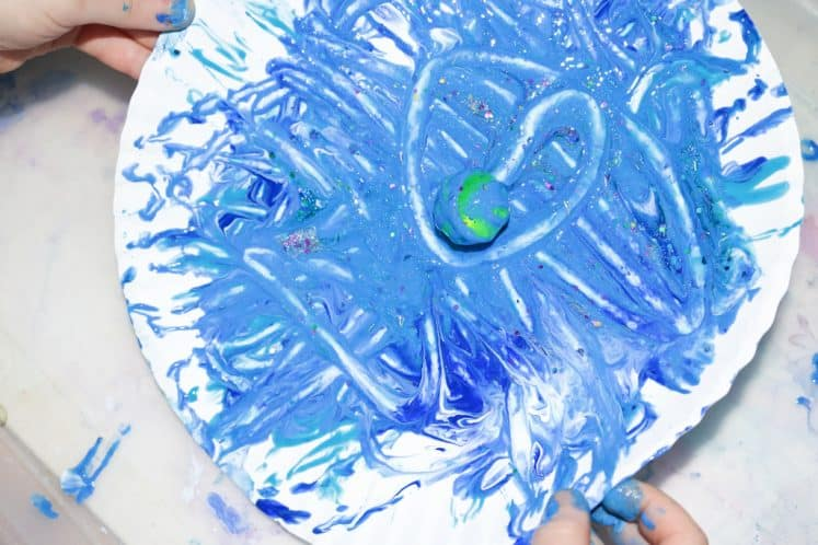 child rotating paper plate with ball and paint