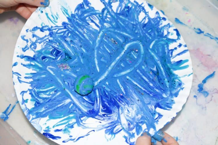 preschooler rotating paper plate with ball and paint to make planet process art