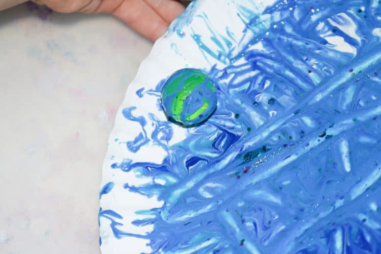 child ball painting on paper plate to make Neptune Painting for Kids