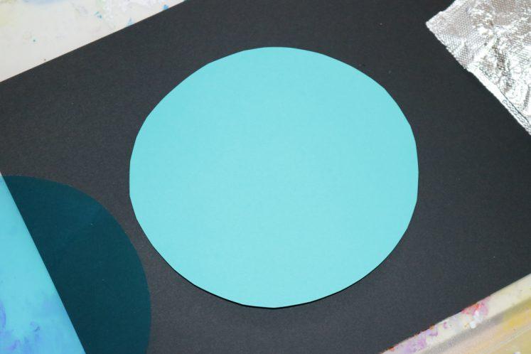 blue cardstock circle on black background