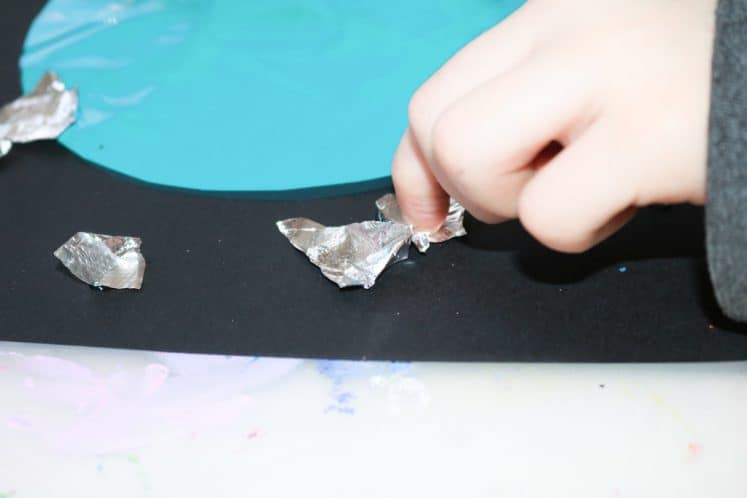 child gluing small pieces of aluminum foil onto black cardstock to make stars for Uranus Process Art