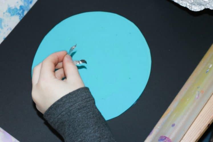 child gluing aluminum foil onto Uranus process art to make stars