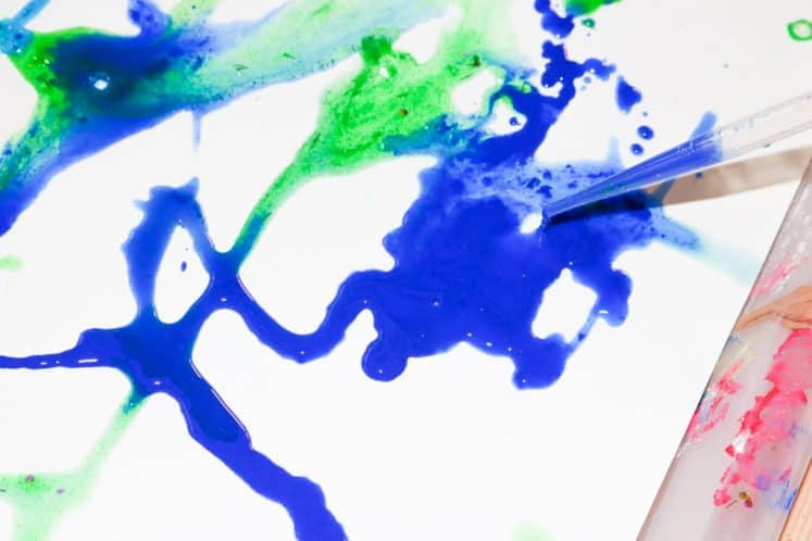 child dripping paint onto cardstock