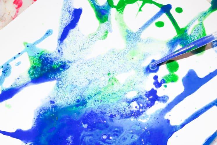 child using eyedropper to drop paint onto salt painting process art