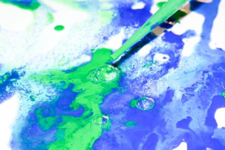 child dripping paint onto salt painting process art