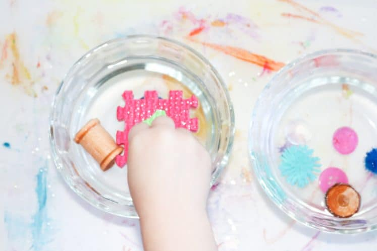 child experimenting with sink or float activity using small bowls of water