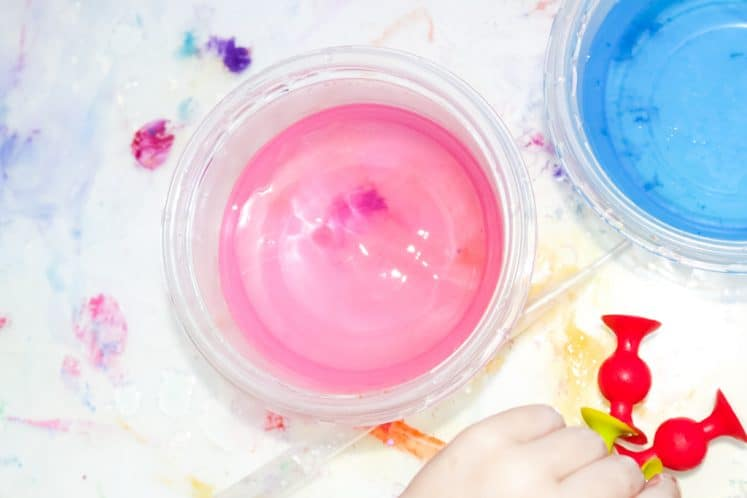 child experimenting with suction cups and colored water