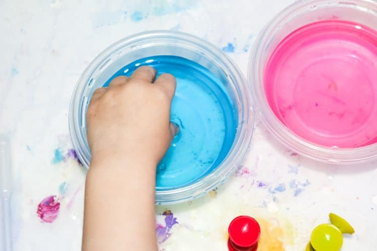 child dipping suction cup into bowl of colored water