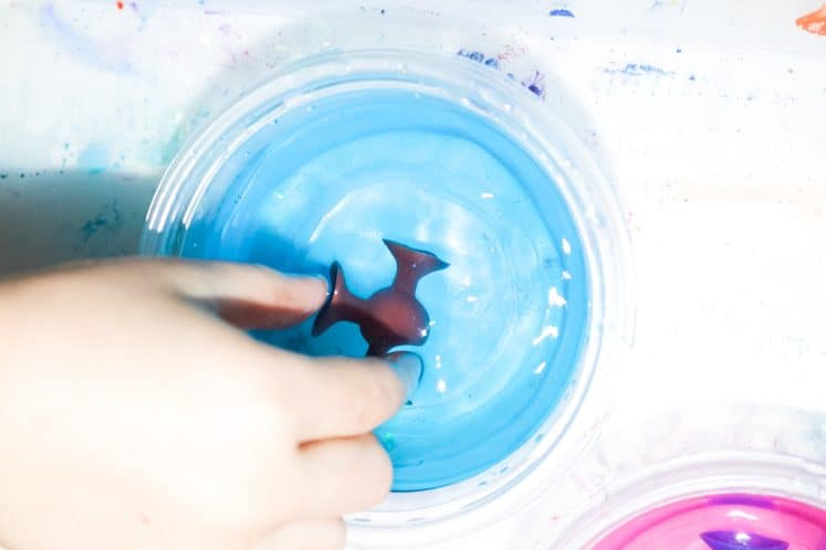 child dipping suction cup toy into water