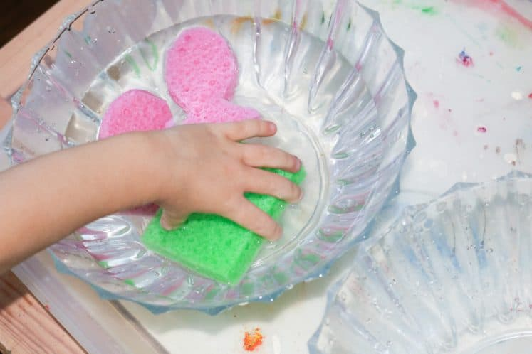 child picking up colored sponge from bowl of water