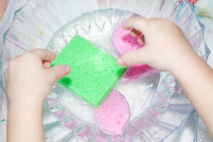 child transferring water between two bowls using sponges