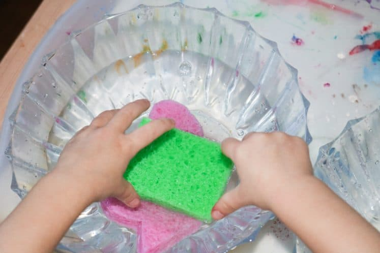 child squeezing shaped sponges into bowl of water
