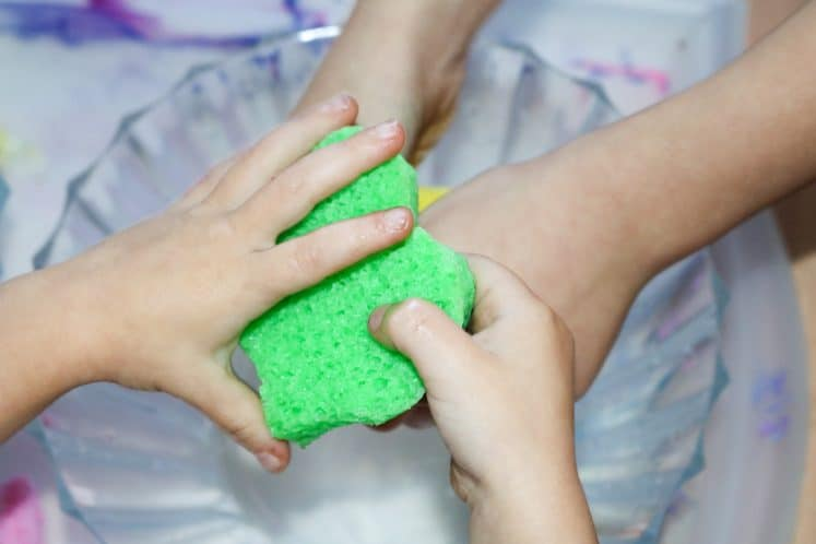 child squeezing sponge to transfer water