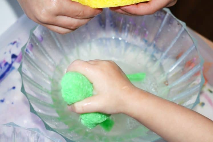 children squeezing sponges to transfer water between two bowls