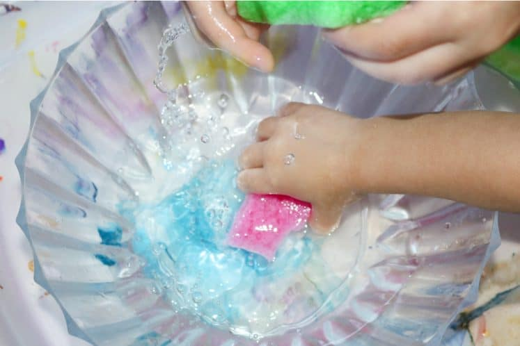 children squeezing sponges into bowl to transfer water