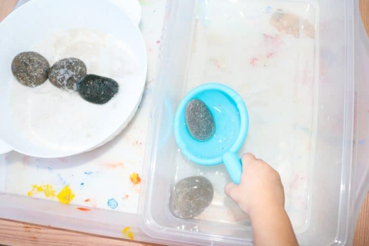 child scooping rock from water bin