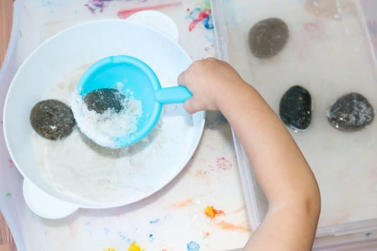 child using plastic scoop to rock from bin of sand