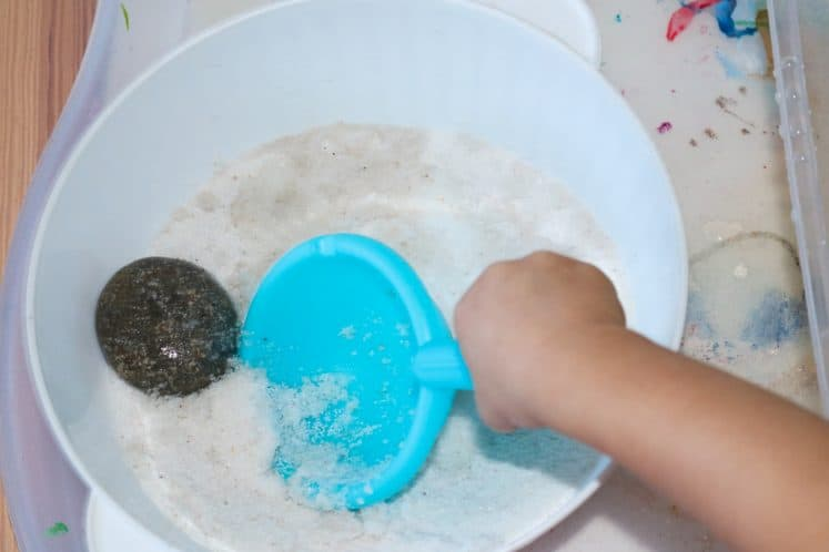 child using plastic scoop to remove rock from container of sand