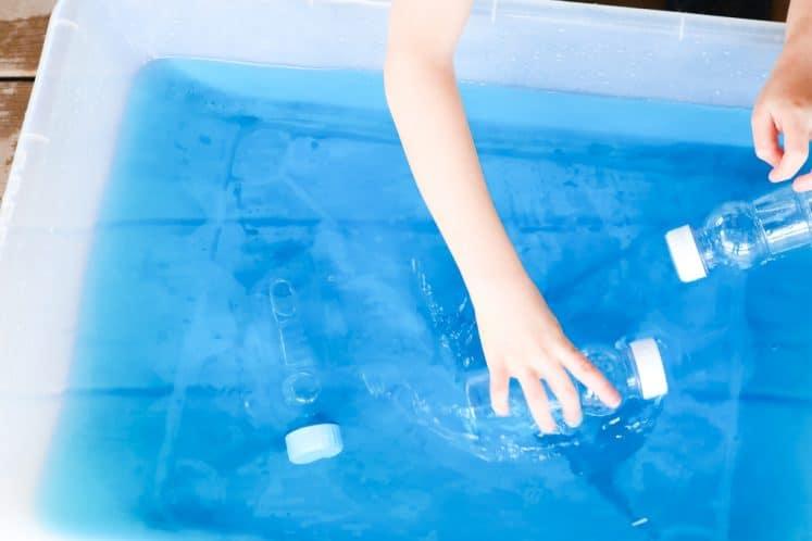 child simulating submarines using plastic bottles in large bin of water