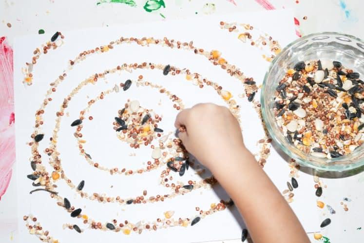 preschooler arranging seeds on seed mosaic craft