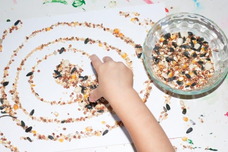 preschooler arranging seeds on cardstock to make seed craft