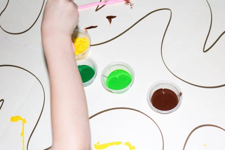 child dipping rubber worm into cup of paint for worm painting