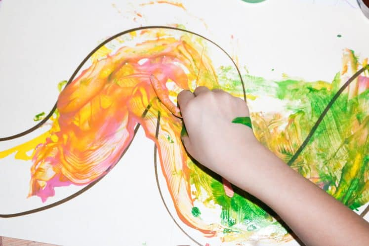 child making worm art with rubber worm and paint