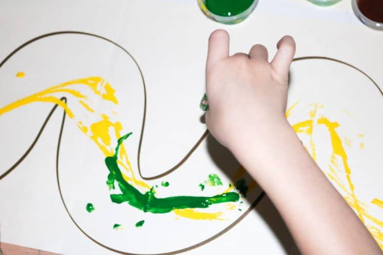 child splattering paint onto paper using rubber worm