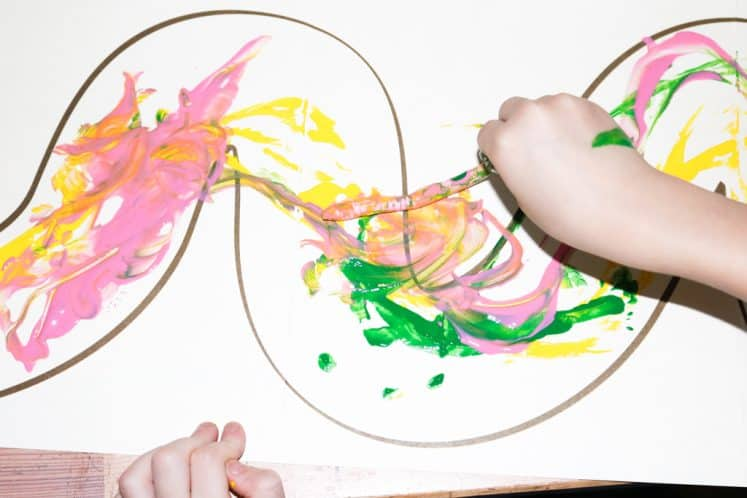 child painting with rubber worm