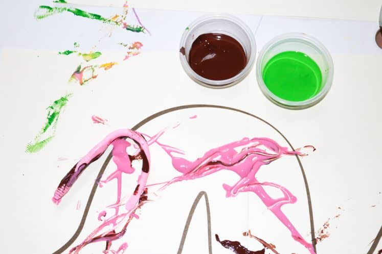 cups of paint and paint-covered rubber worm on worm outline