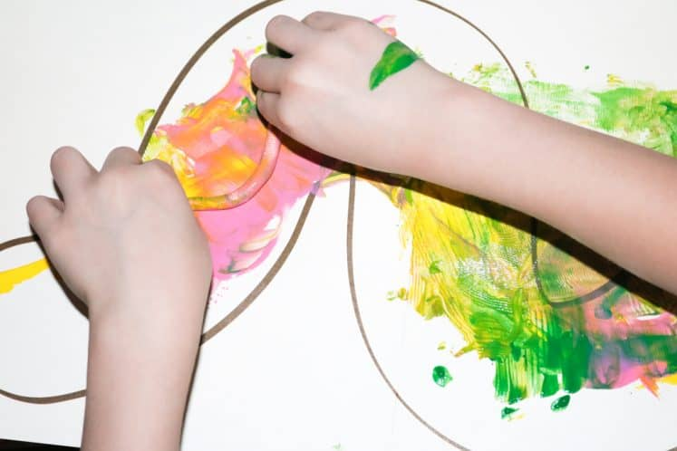 child rolling rubber worm on worm painting for kids