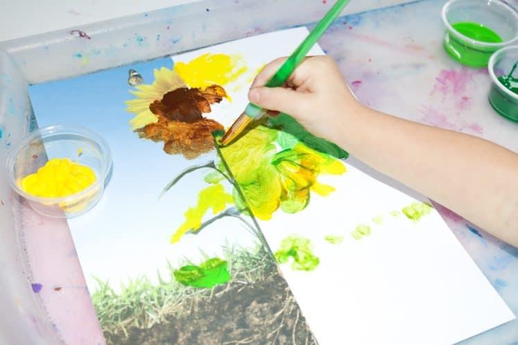 preschooler using paint to finish sunflower painting