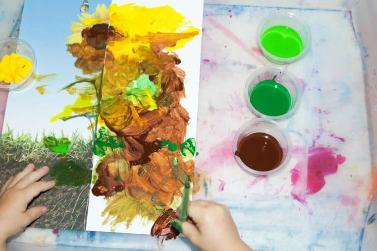 preschooler adding roots to flower painting for kids