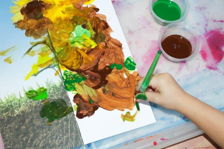 preschooler painting sunflower using half of a photo
