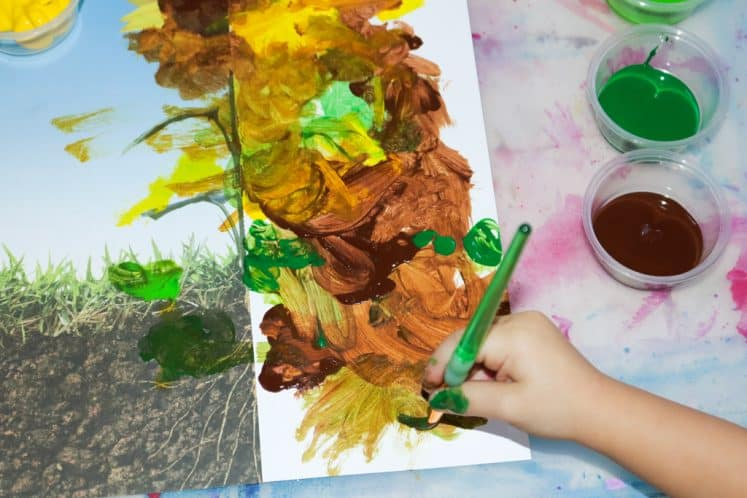 preschooler painting flower using half of a photo